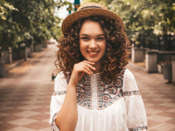 Beautiful smiling model with afro curls hairstyle dressed in summer hipster white dress. Free Photo