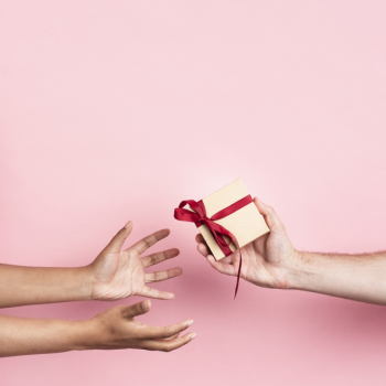 Hands receiving a small wrapped gift with ribbon Free Photo