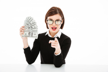 Young businesswoman showing money and pointing with finger Free Photo