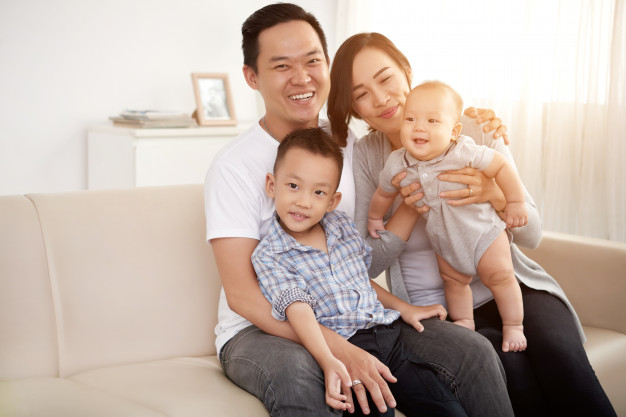 Loving asian couple posing on couch at home with young son and baby Free  Photo - Nohat - Free for designer
