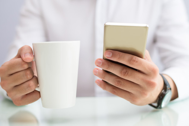 Close-up of businessman drinking coffee and using smartphone - Nohat