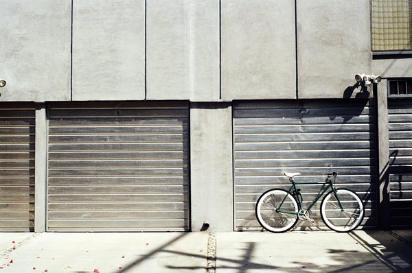 Bicycle on street in front of garage png image transparent background